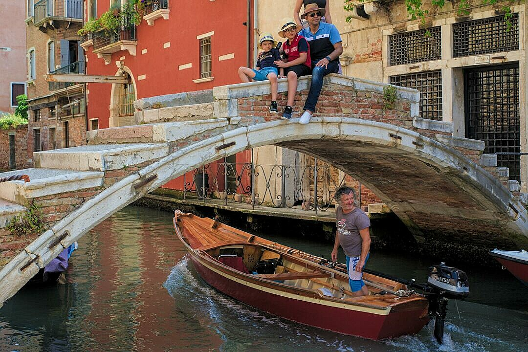 A traditional Sanpierota passing under a bridge in Venice