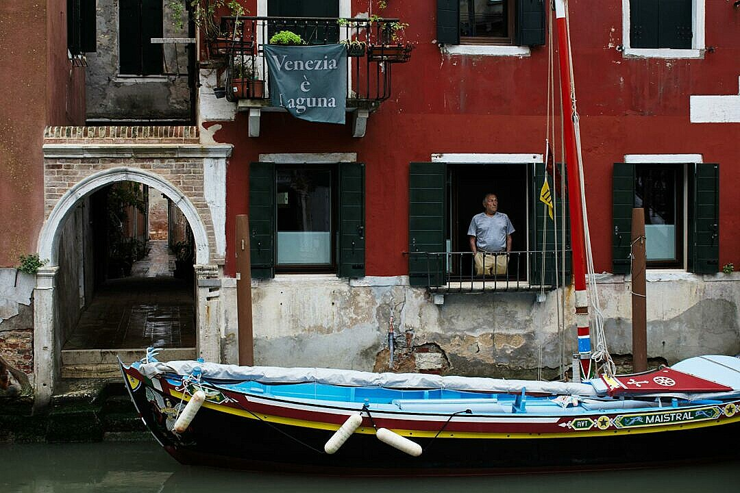 A tradition sailing boat moored under a window in Venice