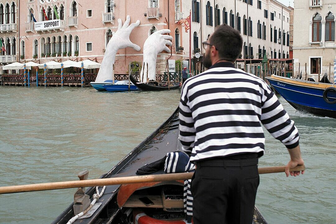 Crossing the Grand Canal with a traghetto with Lorenzo Quinn's giant hands in the background